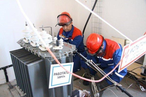 Рабочие осматривают трансформатор